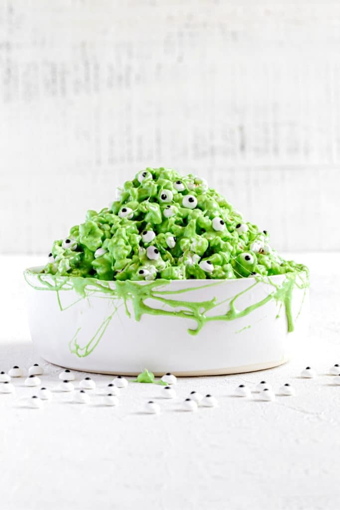 Green popcorn slime in white bowl with stretches of marshmallow slime and spooky candy eyes.