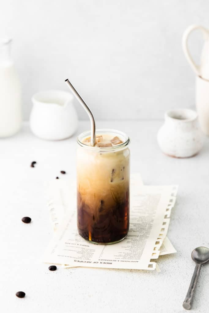 Iced Vanilla Latte Starbucks in a glass with straw next to a metal spoon.