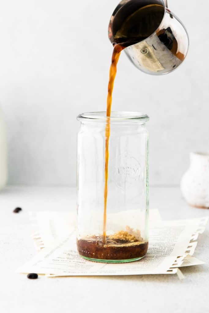 Pouring espresso into a tall glass for making iced latte.