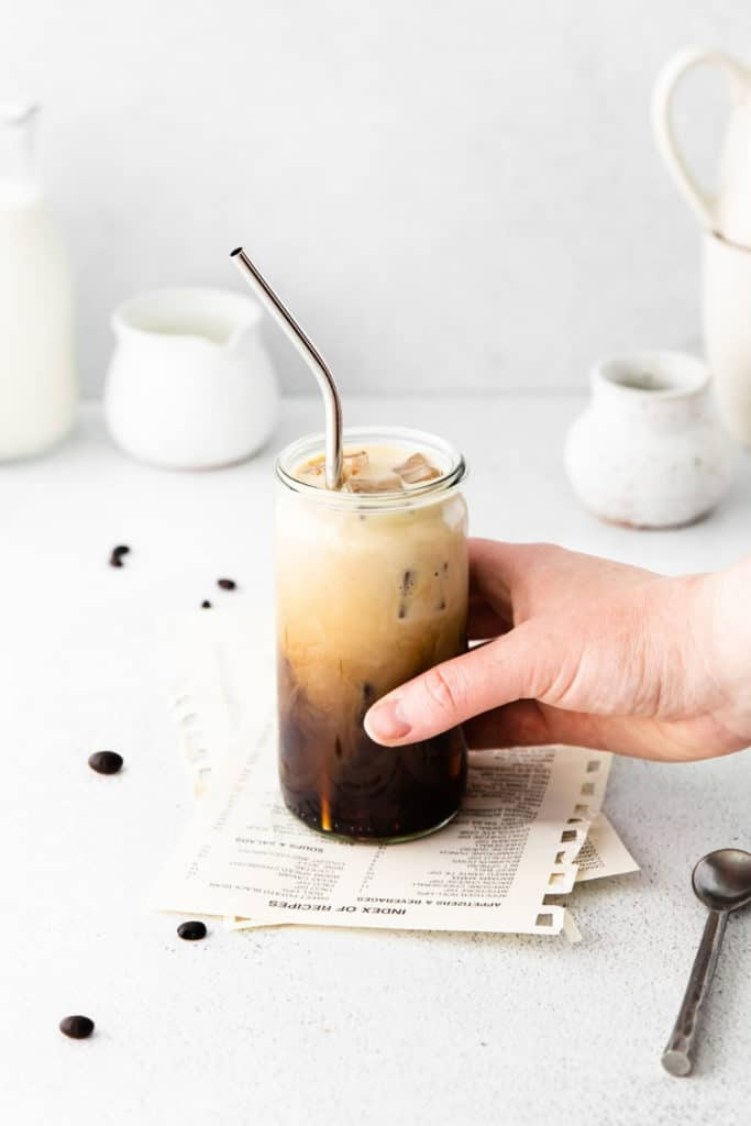 A hand lifting a glass of iced latte from a light-grey tabletop.