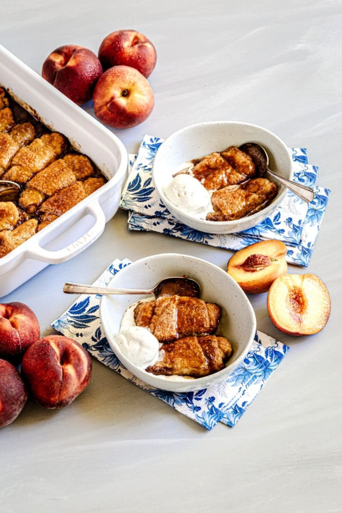Square baker with Peach dumplings and 2 serving portions in bowls with vanilla ice cream.