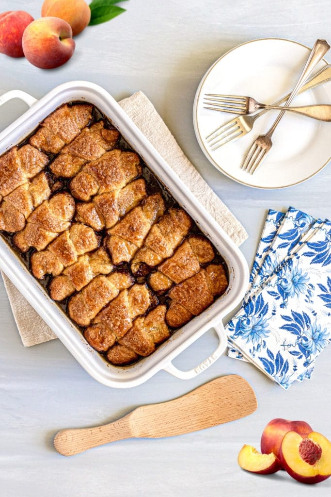 White Staub 9x13 baker with peach cobbler rolls next to blue dessert napkins, plates and forks.