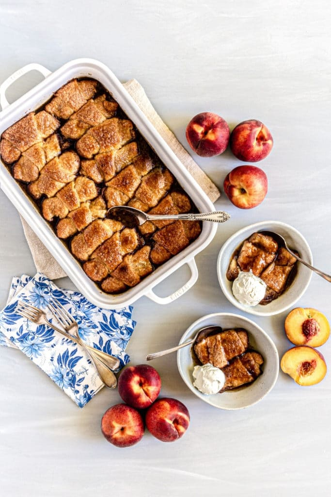 Fresh peaches next to a baking dish with peach dumplings made with crescent rolls and soda.