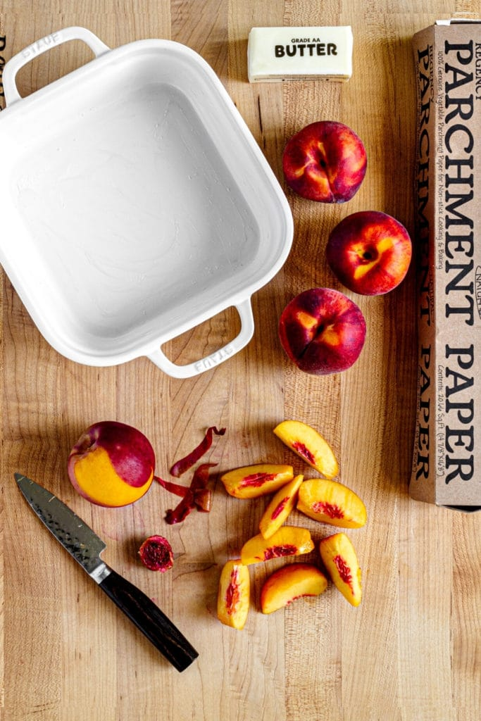 Peaches on a cutting board along with an 8-inch square baker and parchment paper.