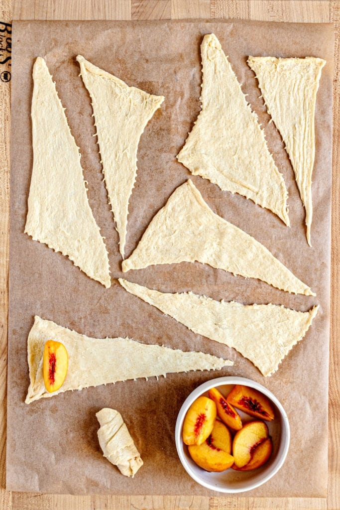 Crescent rolls laid out on parchment paper with sliced peaches for making peach cobbler rolls.