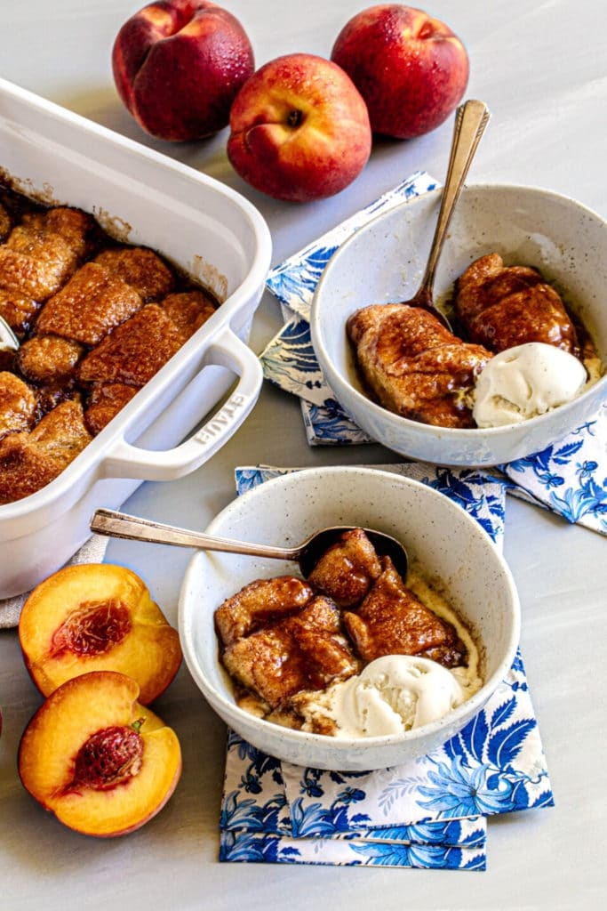 Two servings of peach dumplings with crescent rolls with rounded scoops of vanilla ice cream.