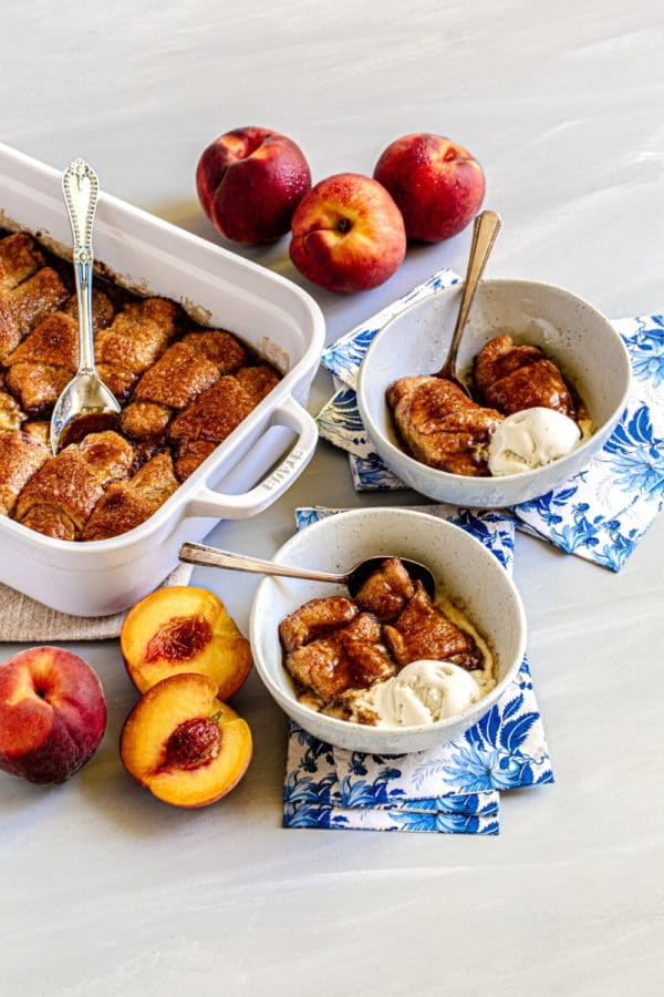White baking dish with peach dumplings alongside 2 bowls of the peach cobbler with crescent rolls and ice cream.