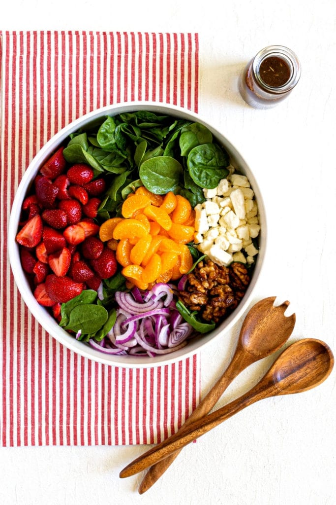 Strawberry spinach salad with feta in a white salad bowl with wooden tongs and balsamic dressing.