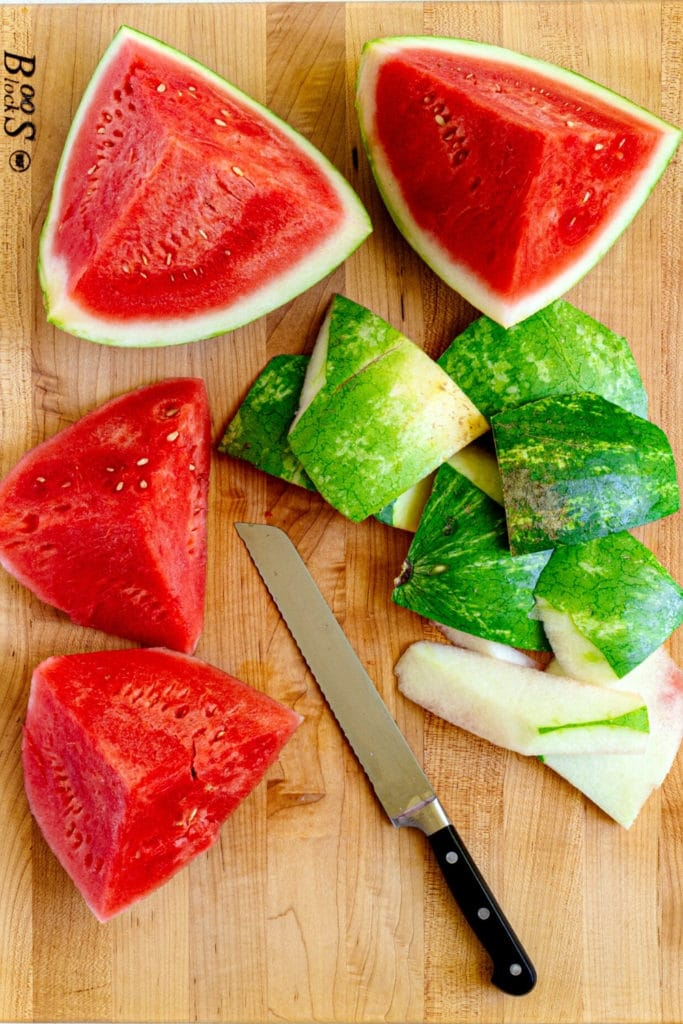 Quartered watermelon on a wooden board with the green rind being sliced off with a knife.