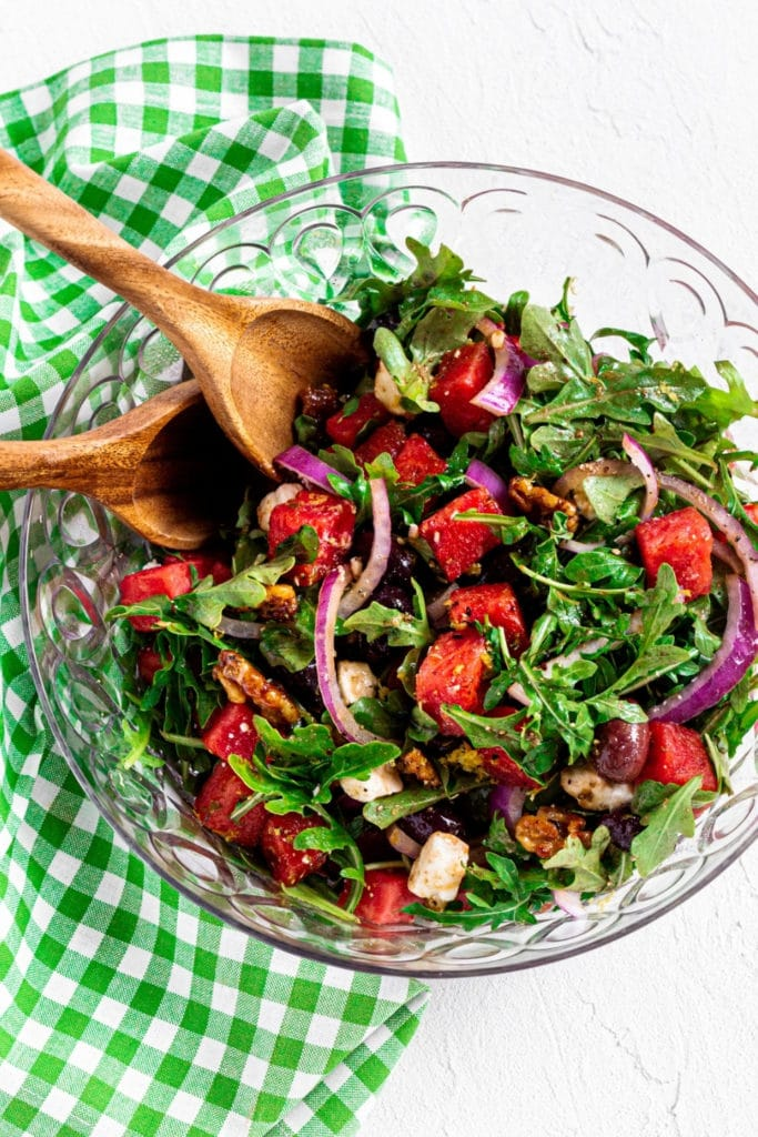Watermelon Arugula Salad with feta cheese in clear-glass salad bowl with wooden servers.