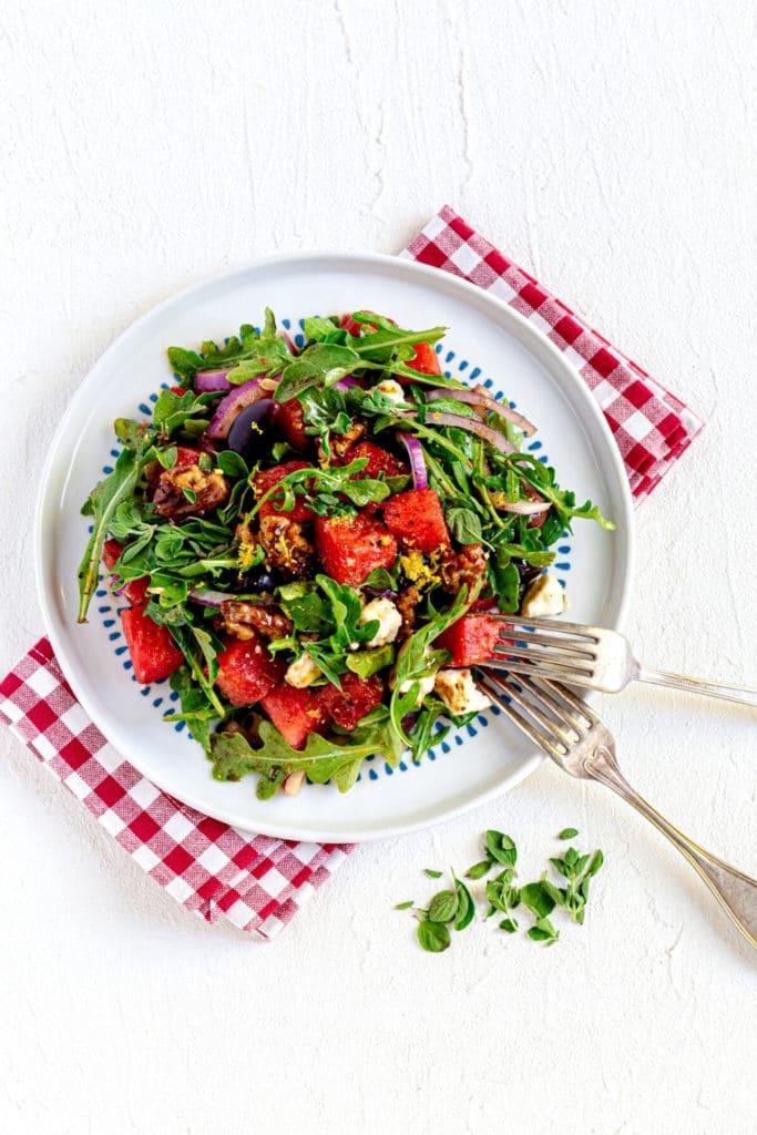 Watermelon arugula salad served on a salad plate with vintage metal forks.
