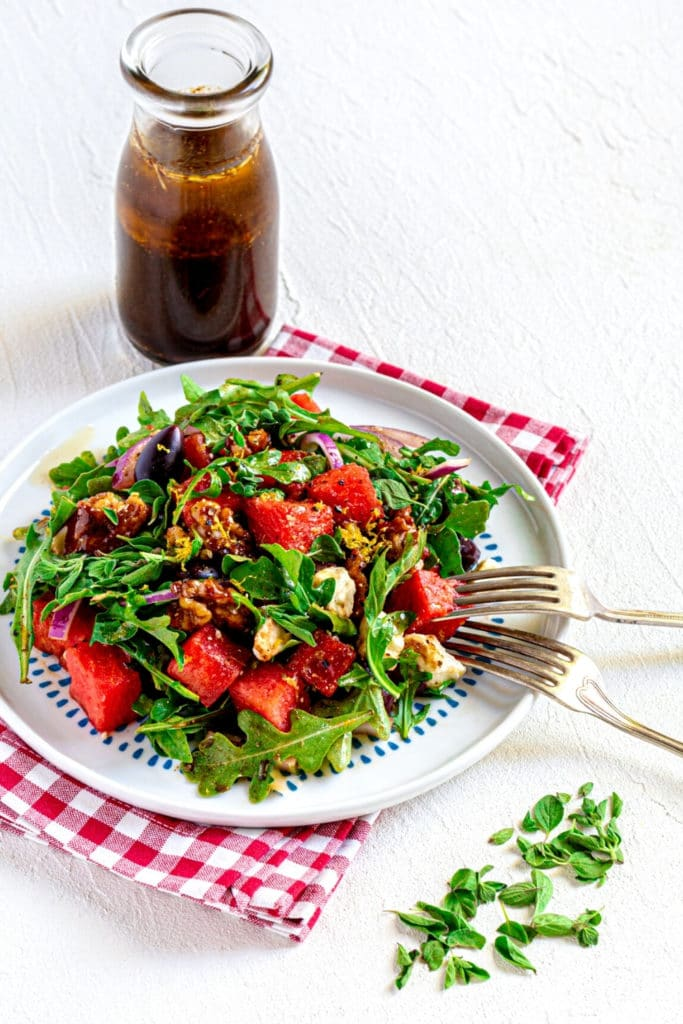 Plated watermelon arugula salad with feta cheese alongside a bottle of balsamic salad dressing.