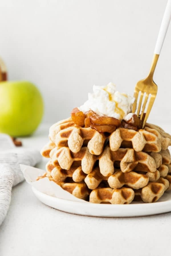 Stack of freshly-made apple cinnamon waffles on a white plate with gold fork.