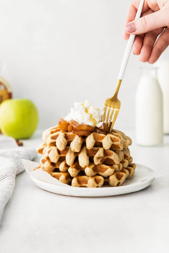 Stack of 4 apple cinnamon waffles with caramelized apple topping and whipped cream on a plate.