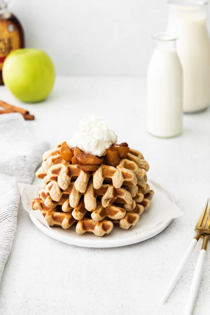 Four cinnamon waffles topped with caramelized apples and whipped cream on a white plate with fork.