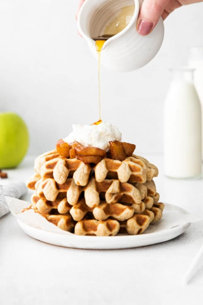 Warm maple syrup being poured over cinnamon waffles topped with apple compote.