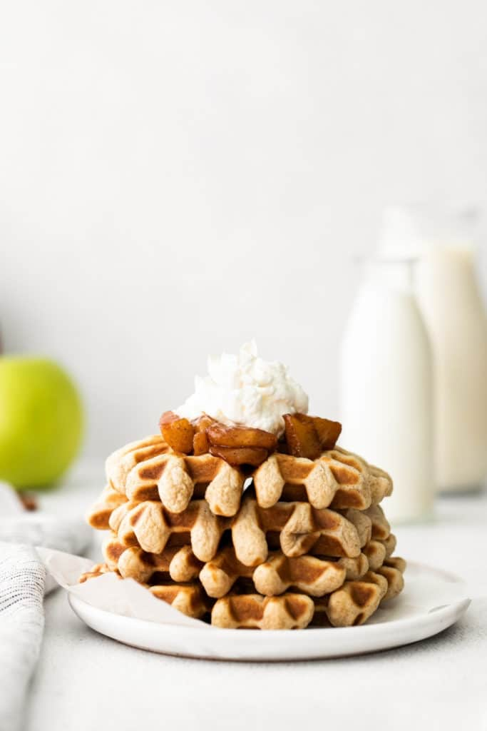 Plate of cinnamon waffles with caramelized apple topping and whipped cream.