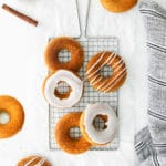 Freshly baked cinnamon donuts with vanilla glaze cooling on a wire rack.