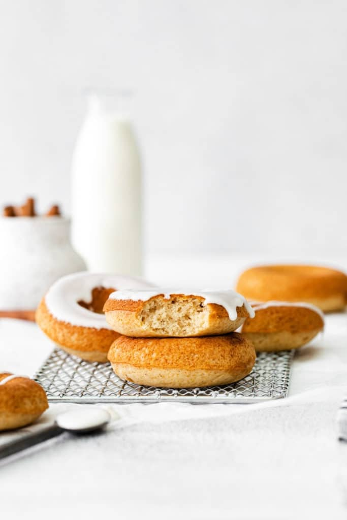 Baked cinnamon donuts with vanilla glaze on a wire rack.
