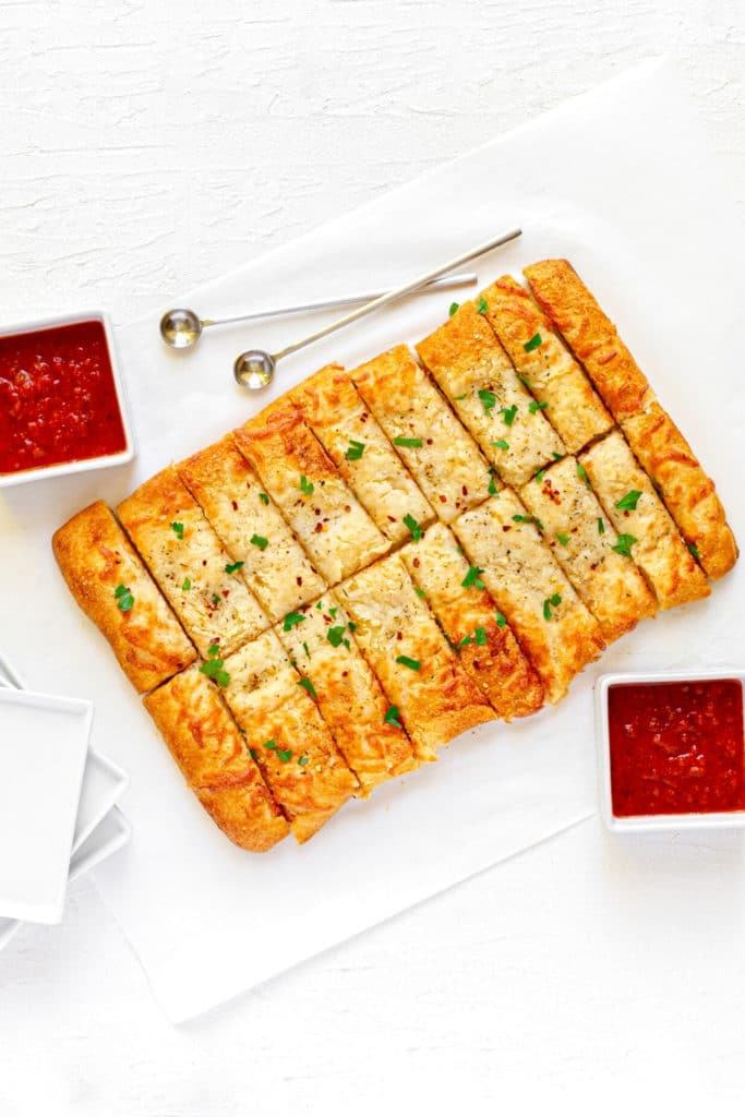 Italian cheesy breadsticks with garlic butter alongside white appetizer plates and pizza dipping sauce.