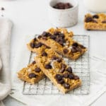 Four chewy chocolate chip granola bars garnished with flaky sea salt cooling on a wire rack.
