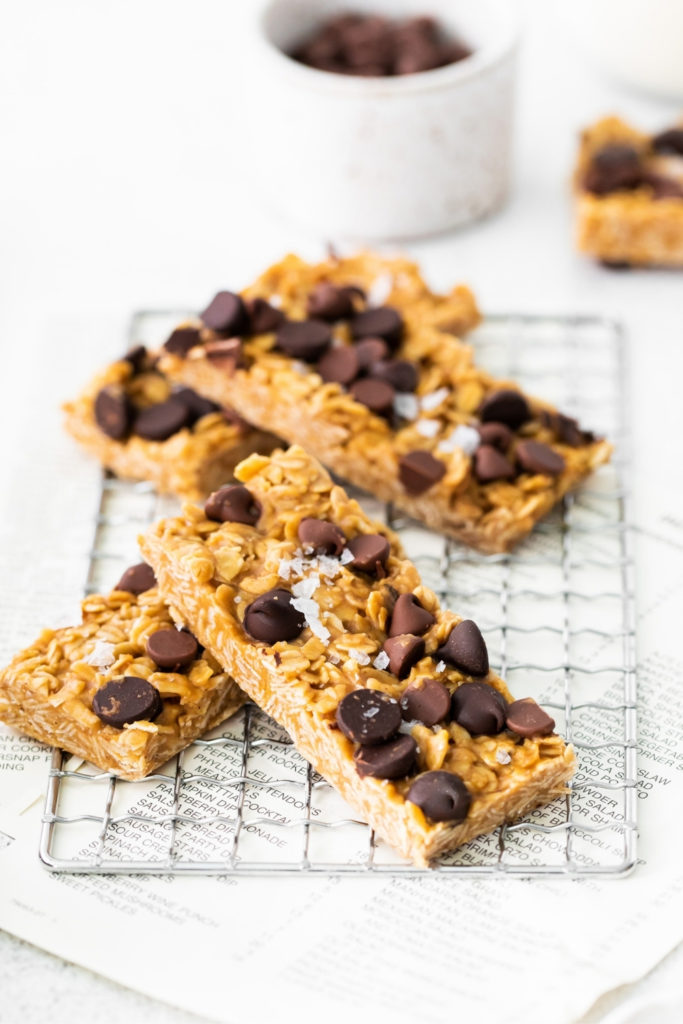 Chewy chocolate chip granola bars sprinkled with flaky sea salt on a small wire rack.