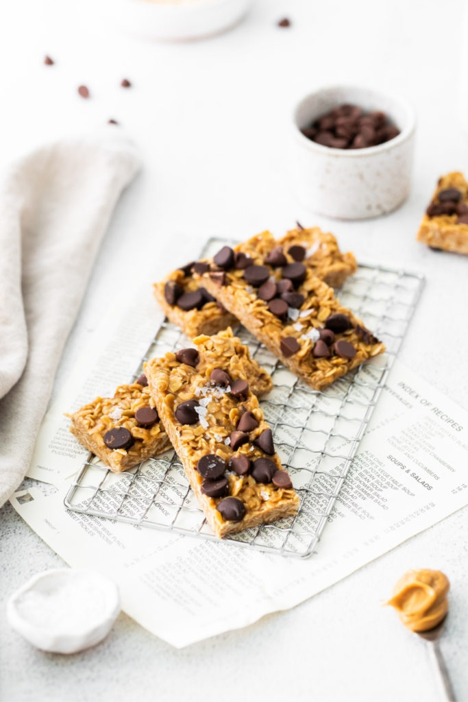 Four chewy granola bars topped with chocolate chips and flaky sea salt on a wire rack.