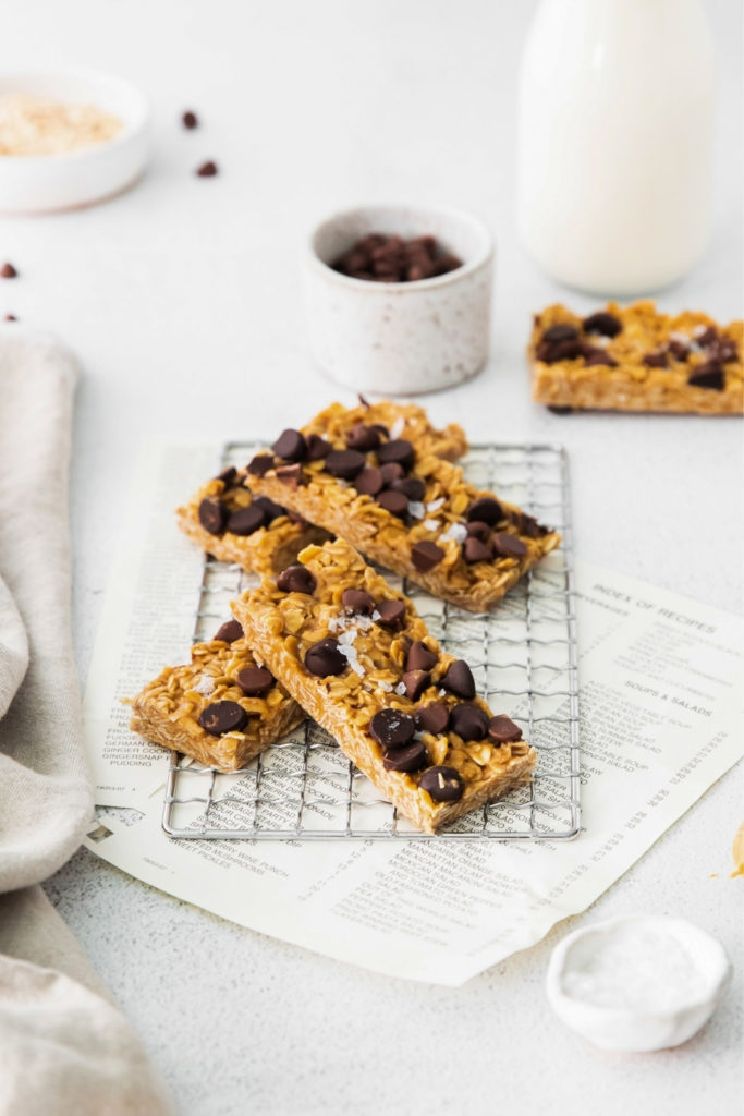 Chocolate chip granola bars cooling on a rack sprinkled with chocolate chips and flaky salt.