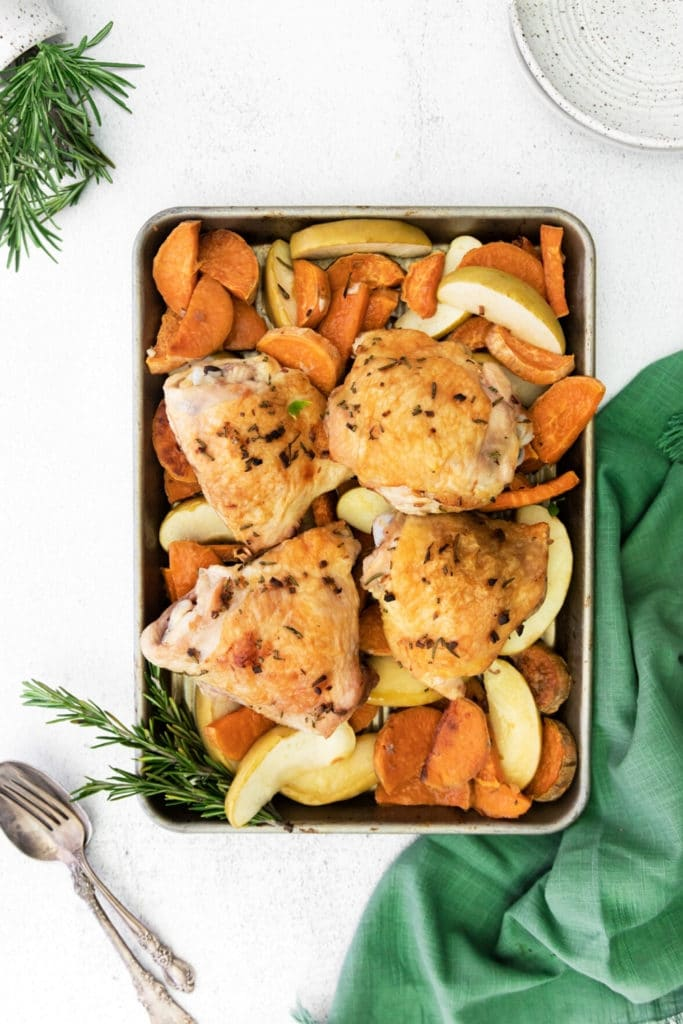 Chicken sweet potato bake sheet pan dinner with apples and rosemary on a tabletop with plates.