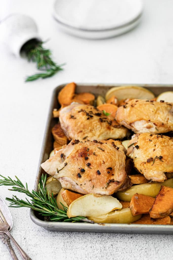 Baking tray with 4 chicken thighs, sweet potatoes and sliced apples with rosemary. This sheet pan meal is served on a table.