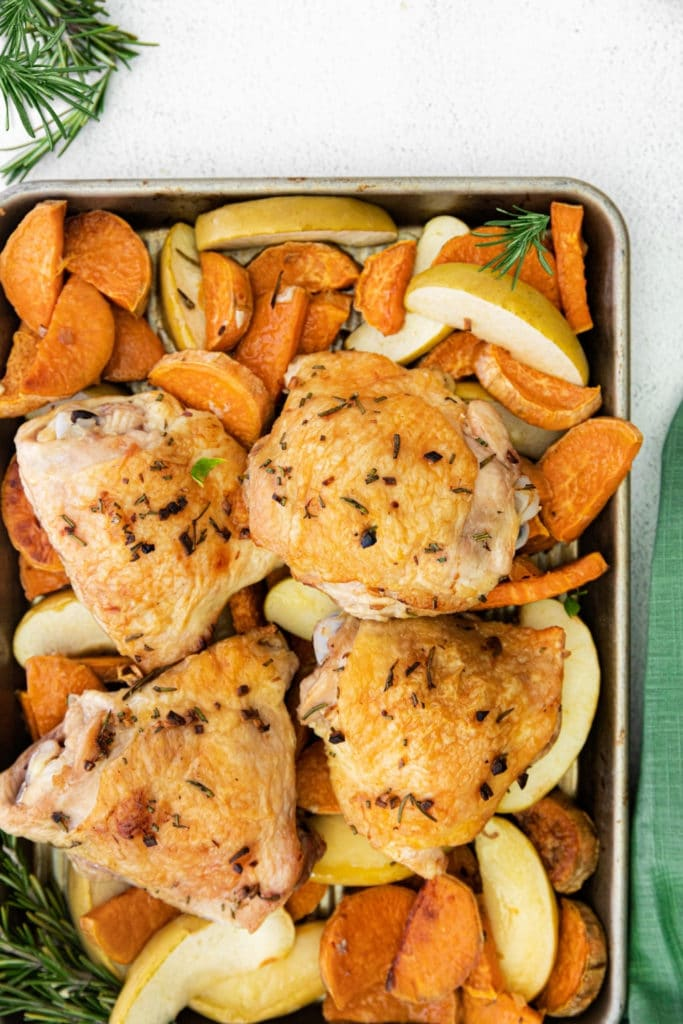 Chicken thigh sheet pan dinner with rosemary, apples and sweet potatoes served in pan on countertop.