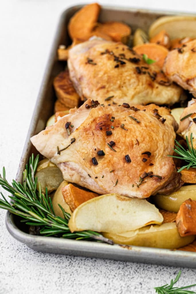 Sheet pan chicken thighs in a baking tray with sweet potatoes, apples and rosemary.