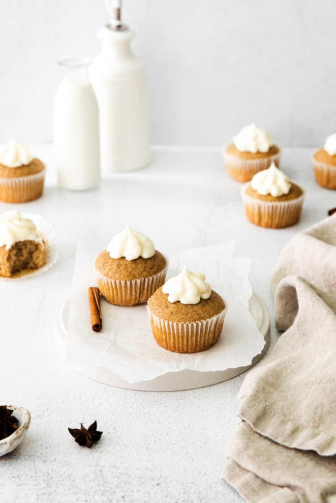 Spice cupcakes with cinnamon and cream cheese icing on a dessert table with linen napkin.