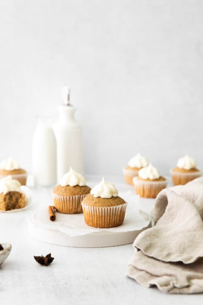 Seven freshly-baked cinnamon cupcakes on marble serving board with cinnamon stick and other spices.