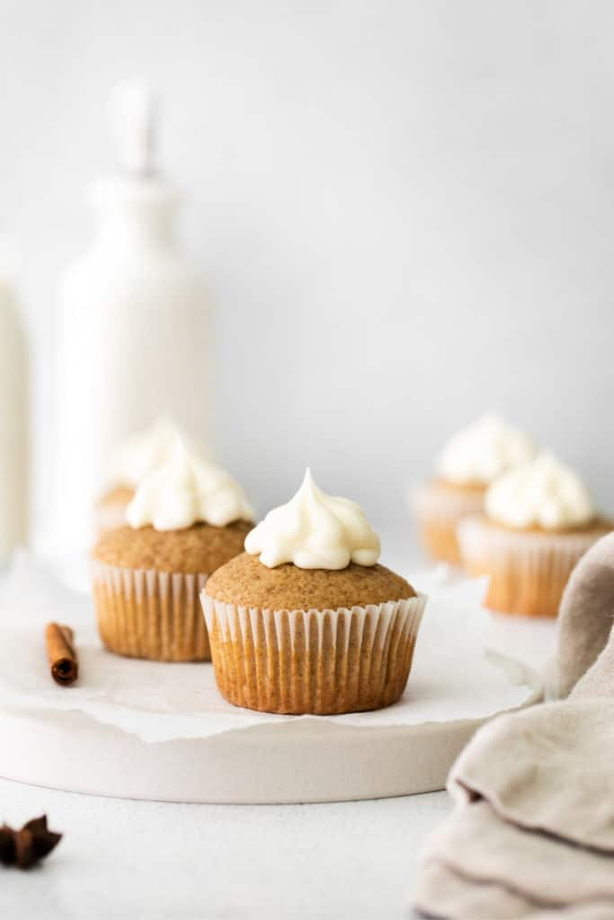 Cinnamon cupcakes with cream cheese frosting on top of a ceramic serving board with linen napkin.