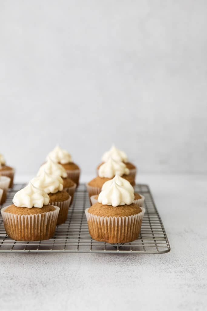 Cinnamon spice cupcakes with dollops of piped on cream cheese frosting on a metal cooling rack.