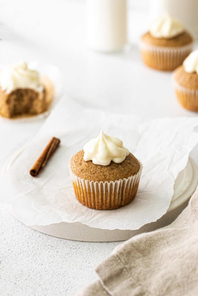 Cinnamon cupcake with a dollop of cream cheese frosting next to a cinnamon stick.