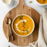 Bowl of creamy butternut squash soup drizzled with heavy cream and sprinkled with pumpkin seeds.