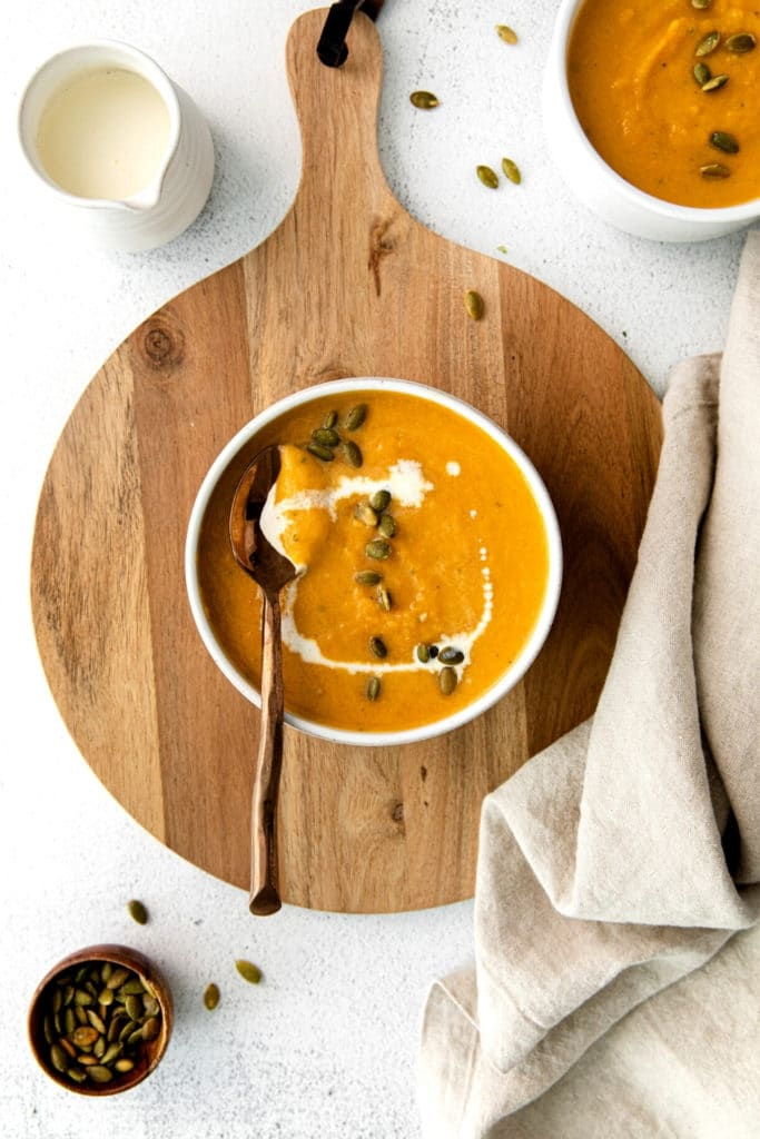 Creamy butternut squash soup in a bowl with copper spoon on a wooden board.