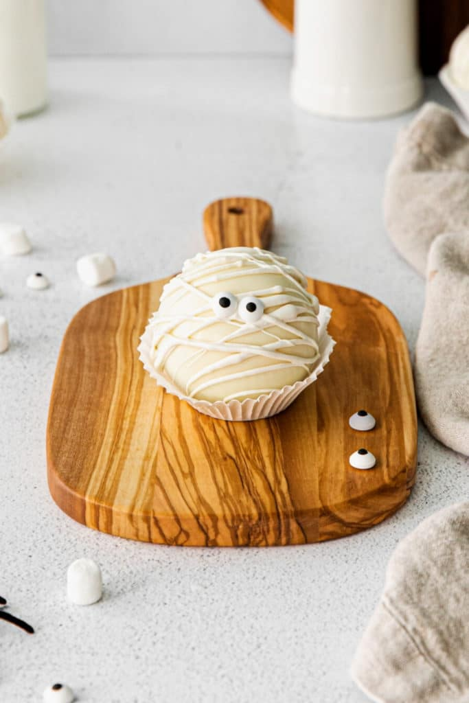 Halloween white hot chocolate bomb on a wooden board with candy eyes.