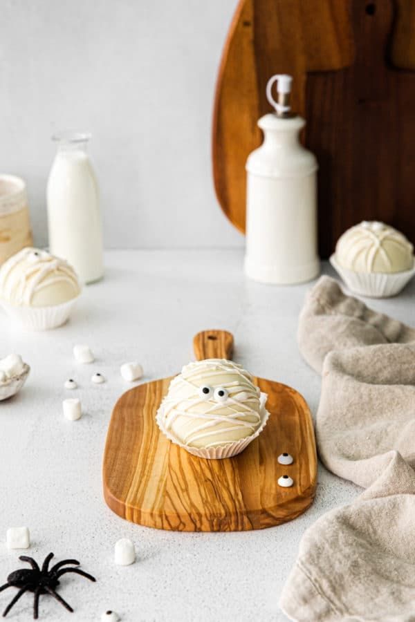 Halloween hot cocoa bombs: little white chocolate bomb mummies with candy eyes on a wooden board.