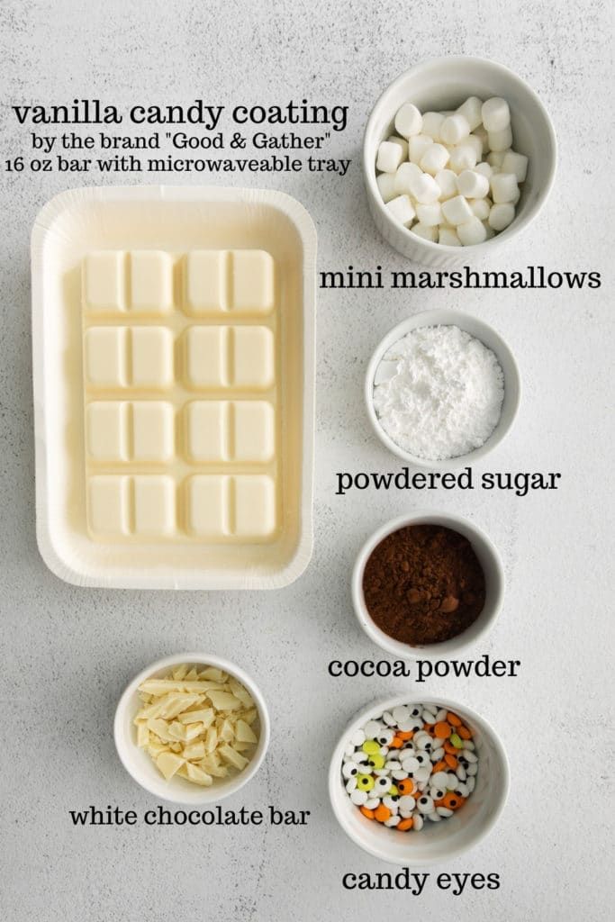 Ingredients for Halloween hot chocolate bombs, specifically white cocoa bomb mummies.