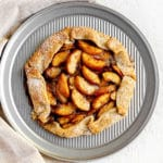 Homemade peach galette on round metal tray.