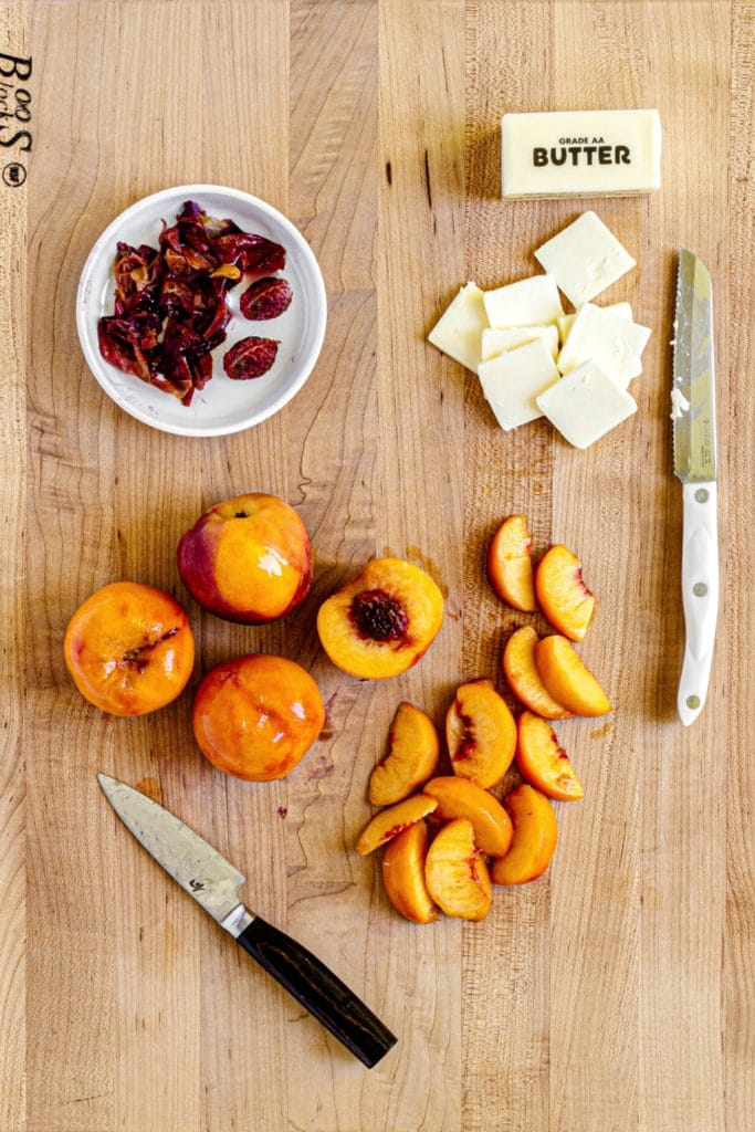 Recipe prep for peach galette: Peel, pit and thinly slice peaches. Slice pats of butter.