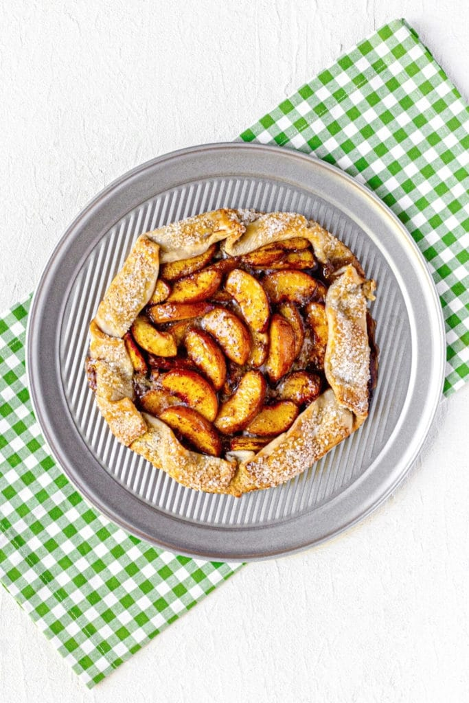 Freshly-baked rustic peach tart on a round metal baking tray.