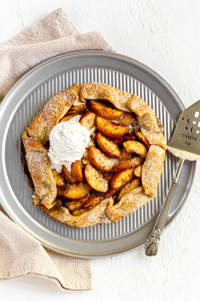 Freshly-baked peach galette with scoop of vanilla ice cream on a round baking tray with vintage pie server.