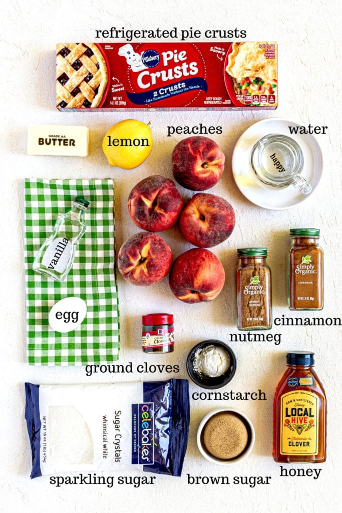 Ingredients for Peach Galette on a white tabletop.