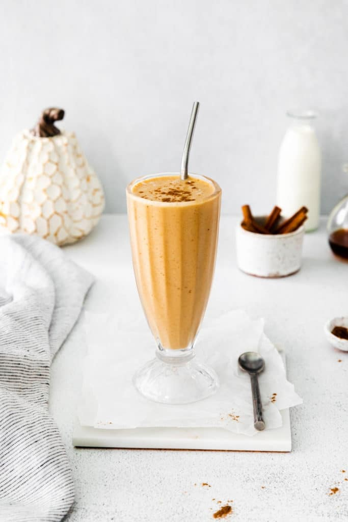 Pumpkin pie smoothie garnished with ground cinnamon. Glass is on a marble coaster.