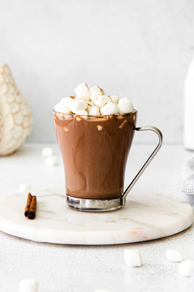 Pumpkin spice hot cocoa in a clear glass mug. Drink is garnished with mini marshmallows.