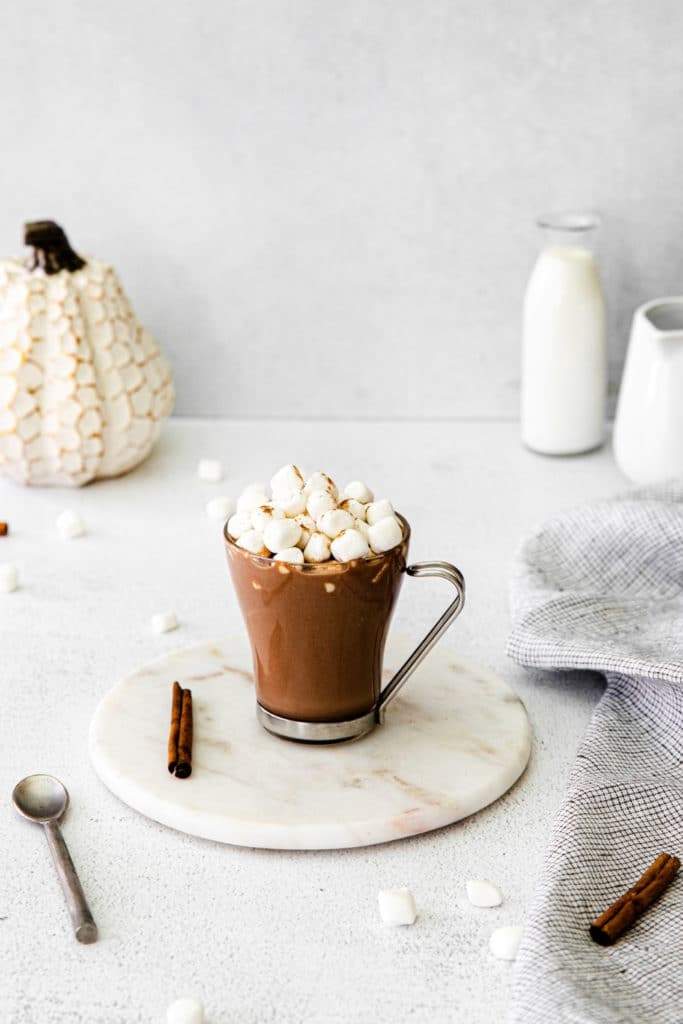 Homemade Pumpkin Spice Hot Chocolate Starbucks on a white marble trivet with metal spoon.